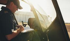 Pilot checking the flight manual before a take off - stock photo