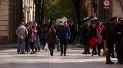Spanish couple come towards across city square, telephoto view Stock Footage