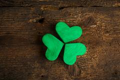 Green shamrock clovers on wooden background - stock photo