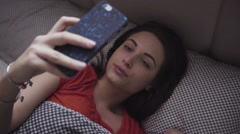 Young woman lying in a bed and using her mobile device. Girl looking at the Stock Footage
