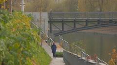 Woman walking by Ljubljanica River in Ljubljana Stock Footage