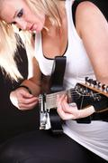 Young woman playing guitar. - stock photo