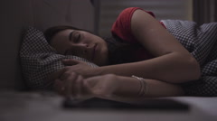 Young woman is sleeping in a cosy bed and then awakes and starts to use her - stock footage