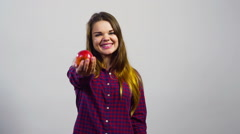 Young girl offer fresh apple and thumb up in front of white wall Stock Footage