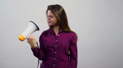 Young girl use megaphone in front of white wall Stock Footage