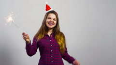 Young girl with christmas hat and sparkler happy emotion in front of white wall Stock Footage