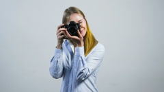 Smiling young girl taking pictures with a camera in front of white wall Stock Footage