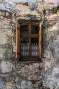 Vintage window with wooden shutters on the stoned house - stock photo