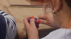 Senior Woman is Doing Violet Easter Egg Cutting Out a Pattern With Knife Stock Footage