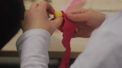 Kid is Rolling up a Red Paper Flower Making Paper Bouquet Sitting at the Table Stock Footage
