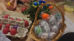 People Doing Easter Eggs Bascket of Colored Eggs on Table Stock Footage
