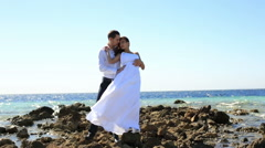 Beautiful wedding couple on the stoned beach . Honeymoon in Egypt. Sea Stock Footage