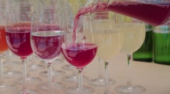Cranberry juice is poured into glasses Stock Footage