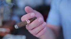 Man holding a fuming cuban cigar - stock footage