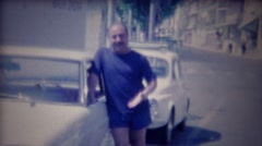 1963: Balding Italian chauffeur man enters classic white Fiat car. Stock Footage