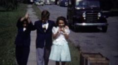 1954: Kids walking sidewalk classic 50's European Jeep style car. - stock footage