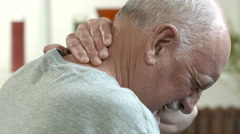 Older man rubbing his painful neck - stock footage