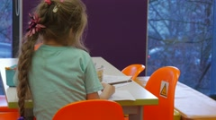 Kid is Drawing With Her Back to Camera Colorful Pencils Paper on a Table Kid is Stock Footage