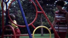 1974: Toddler climbs jungle gym colorful steel playground park. - stock footage