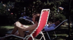 1974: Man gives hippie peace hand sign lounging lawn chairs. - stock footage