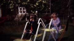 1974: Girls ride backyard playground rocking see saw toy. Stock Footage