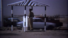 Stock Video Footage of 1974: Traffic checkpoint police guards roof shade structure.