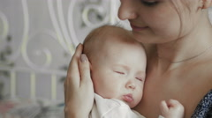 Young Mother Holding her Newborn Sleeping Child. Family at home - stock footage