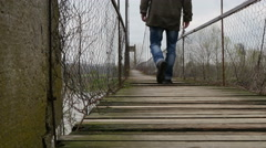 The man trampled  the boards and rocking suspension bridge, dolly shot. Stock Footage