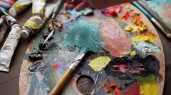 Closeup of paintbrush in woman hands mixing paints on palette - stock footage