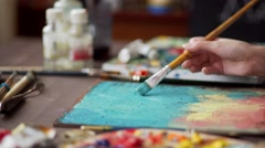 Artist paints a picture of oil paint brush in hand with palette closeup. Stock Footage