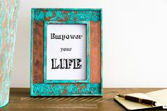 Vintage photo frame on wooden table with text EMPOWER YOUR LIFE Stock Photos