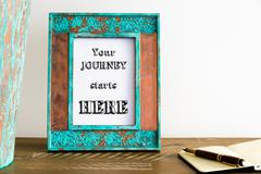 Vintage photo frame on wooden table with text YOUR JOURNEY STARTS HERE - stock photo