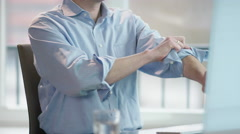 Business man at office desk rolling up left sleeve, stretching fingers Stock Footage