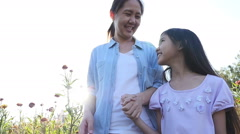 Happy Asian girl walking with her mother in the flower field with sunlight, Slow Stock Footage