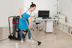 Female Janitor Cleaning Floor With Vacuum Cleaner In Office - stock photo
