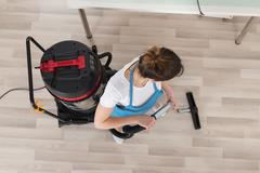 Young Female Janitor Cleaning Wooden Floor With Vacuum Cleaner Stock Photos