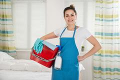 Portrait Of Happy Female Housekeeper With Cleaning Equipment - stock photo