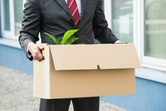 Close-up Of Unemployed Businessperson Carrying Cardboard Boxes - stock photo