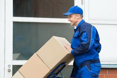 Mature Happy Delivery Man Carrying Boxes On A Hand Truck On Street Stock Photos