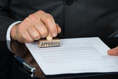 Close-up Of Businessman Hand Stamping On Approved Contract Form On Desk Stock Photos