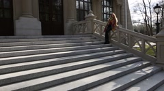 Portrait of a young teenage girl sitting on the front stairs of the old building Stock Footage
