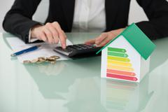 Close-up Of A Businesswoman Calculating Invoice With Euro Coins And Energy Ef Stock Photos