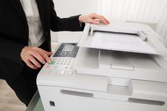 Close-up Of Businesswoman Pressing Printer's Button In Office - stock photo