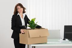 Stock Photo of Sad Young Businesswoman Packing Her Belongings In Box On Desk