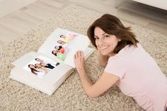 Happy Young Woman Lying On Carpet With Family Photo Album Stock Photos