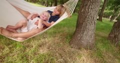 Mischievous siblings having fun on a hammock at park - stock footage