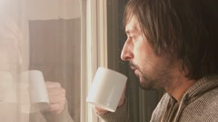 Unshaven male looking through window and drinking coffee - stock footage