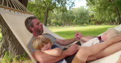 Modern dad hugs his blond child on hammock in garden Stock Footage