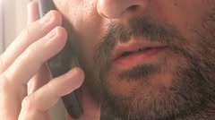 Casual unshaven man talking on mobile phone - stock footage