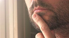 Close up of unshaven male thinking by the window - stock footage